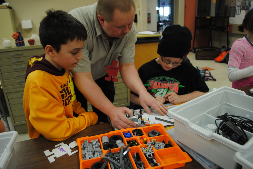 LEGO Robotics instructor Steve Lindquist assists Tony Kreklau, left, and Cooper Reed with one of the steps in building their robot. In the class, students model real-life mechanisms and use creativity, logic and problem-solving skills while learning STEM (Science, Technology, Engineering and Math) concepts.  (Photos by Dana Pavek, WDC Schools)