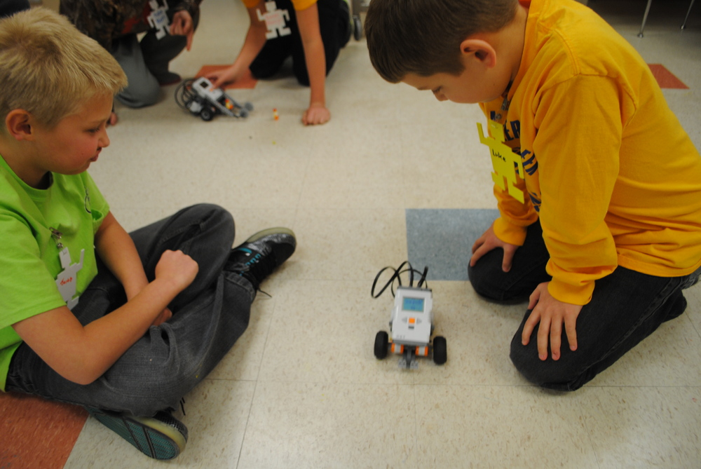 Above, Jacob Lepper, left, and Luke MacDonald try out one of the robots they built and programmed.