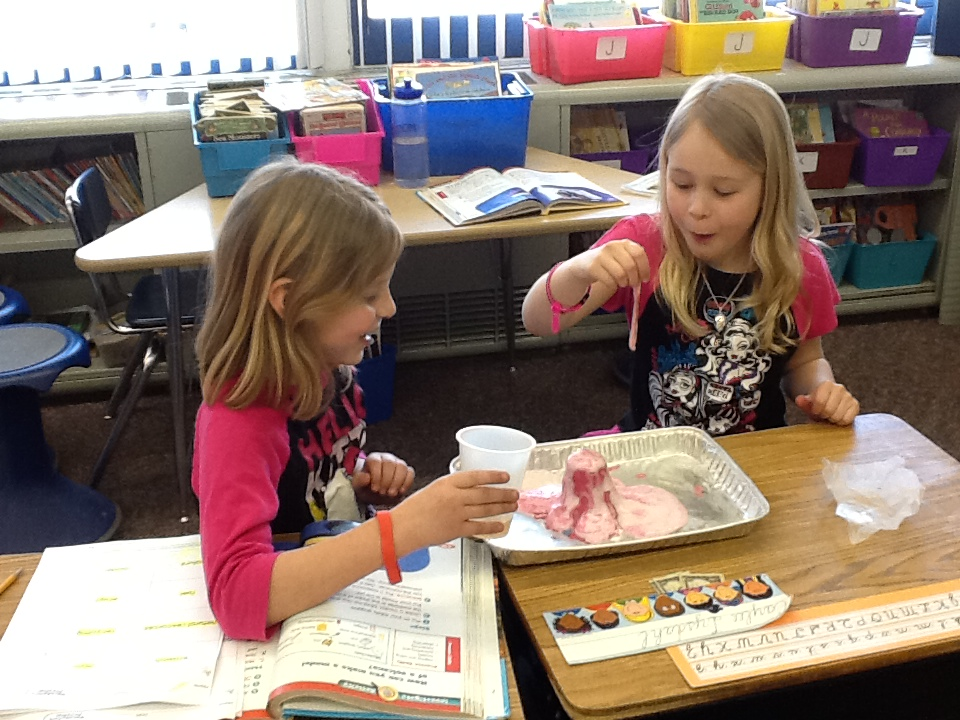 Madeline Safford and Caylee Lysdahl are amazed by their erupting volcano. Students added red food coloring to represent the lava overflowing from their volcano made of a cup and clay.