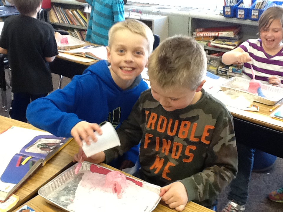 Hogan Jasicki and Jaxson Brown begin pouring the vinegar into their volcano, causing the volcano to erupt!