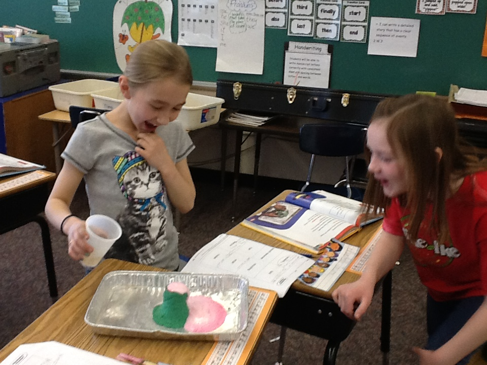Isabelle Larson and Abigail Haman react to their volcano overflowing.
