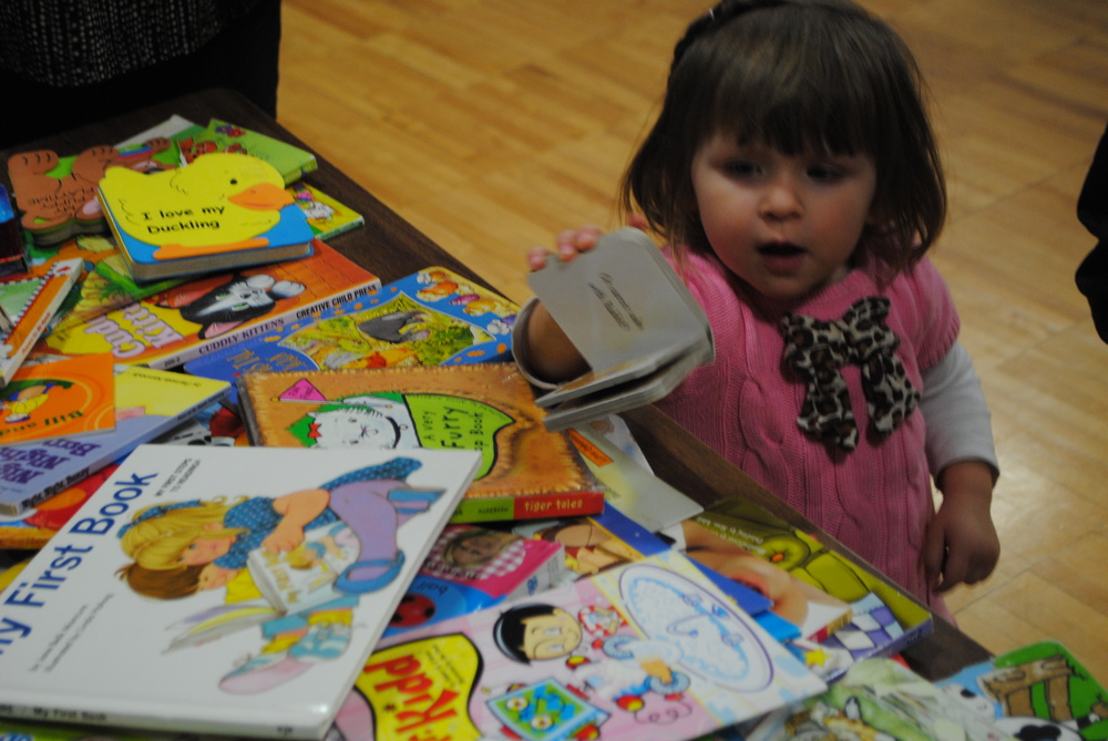 Claire Mumm, 2, selects a book at the book swap during Ice Cream for Books Thursday evening at Wadena-Deer Creek Elementary. Claire is the daughter of Ashley and Randy Mumm of Wadena. (Photos by Dana Pavek, WDC Schools)