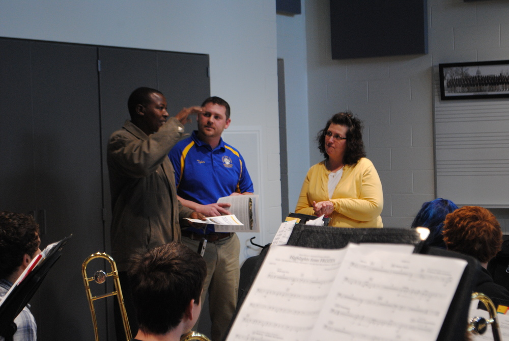 Boke explains to WDC Band Director Lisa Weniger that they do not offer band as a class at his school in Kenya. Also pictured, middle, is Tyler Church, WDC Principal.