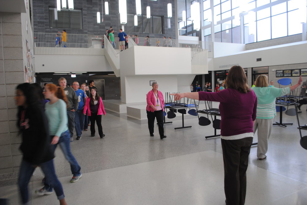 WDC Middle/High School counselor Toni Kraska (in purple) and Spanish teacher Brenda Thelen (in green) direct students and staff to the Auxiliary Gym Thursday afternoon during the statewide tornado drill. (Photos by Dana Pavek, WDC Schools)