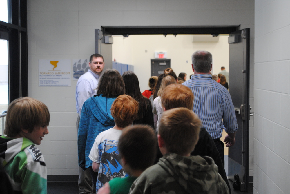 WDC Middle/High School Principal Tyler Church (by doorway) watches and directs fifth-grade students into the Auxiliary Gym during the statewide tornado drill.
