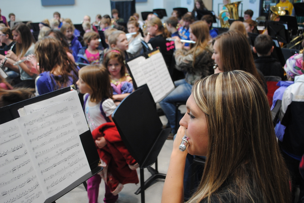 Flutist Morgan Zeise plays as Kindergartners file by and watching closely to their performance.