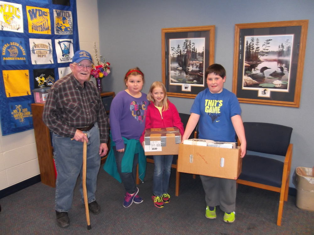 From left, Helmer Grewe and WDC students Hannah Plautz, Cecilia Lindquist and Grant Baron helping carry the nicely boxed pop tabs donated by Mr. Grewe.  (Photo by Lisa Schmidt, WDC Elementary)