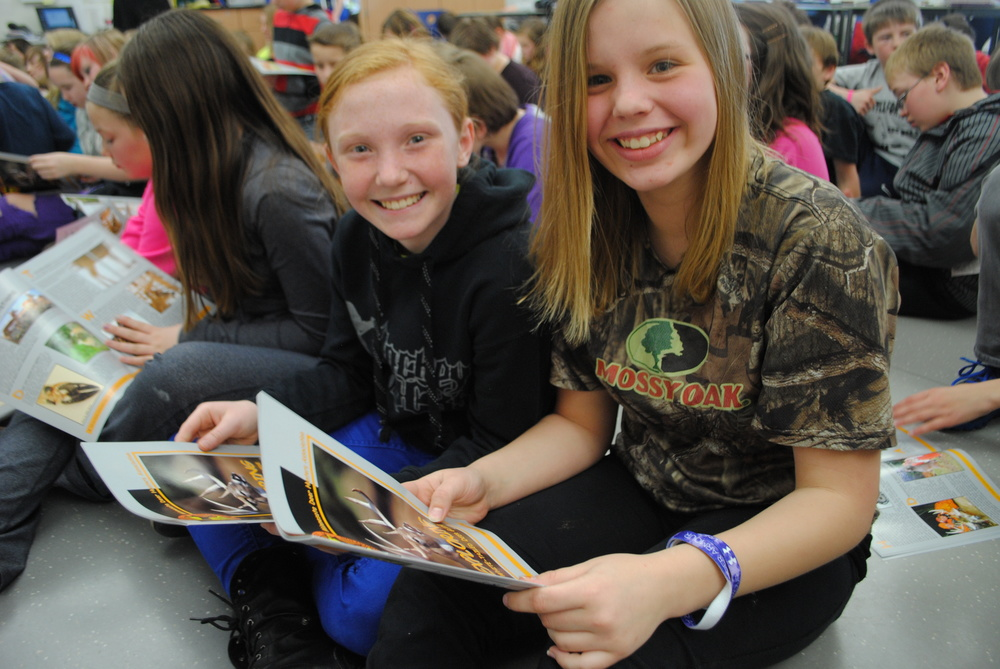 "WDC sixth-graders Courtny Warren and Kylee Ova were all smiles after receiving their ""White-Tailed Deer Guide"" from John Edinger."