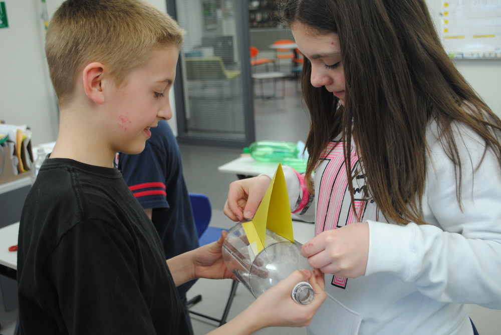 Building the bottle rockets sometimes requires help from a classmate. Above, Elliot Doyle, left, holds the bottle while Joslynn Judd positions the fin.