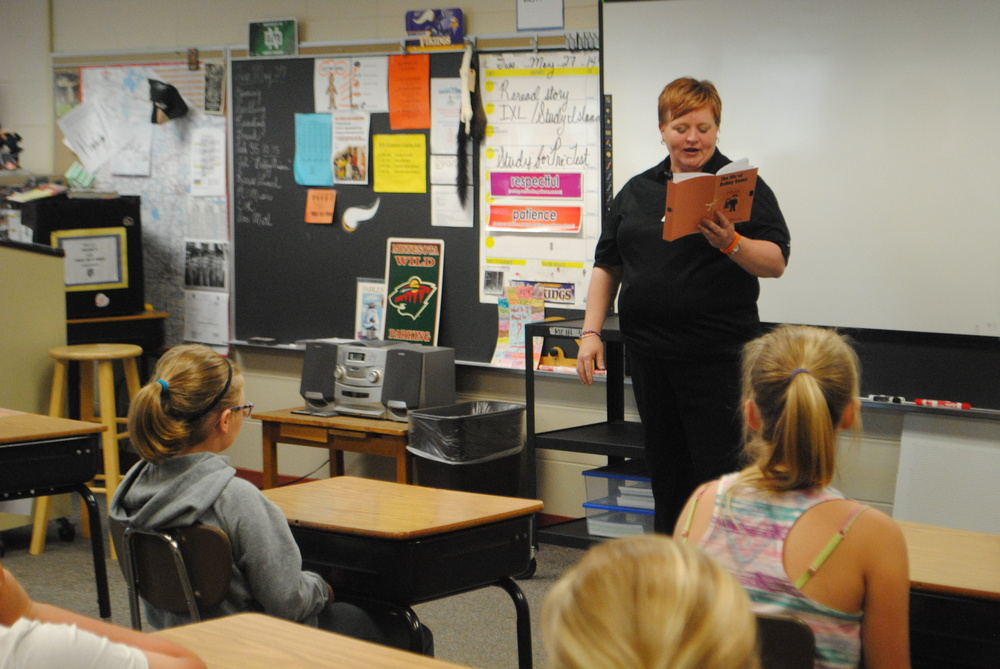 Jil Fiemeyer reads the book started by her daughter Jane and finished in her memory by her classmates in Mr. Mehl's fourth-grade class on Tuesday. It was the first time the students had heard the entire book, where each student wrote a chapter about Bobby Quinn, the character created by Jane.