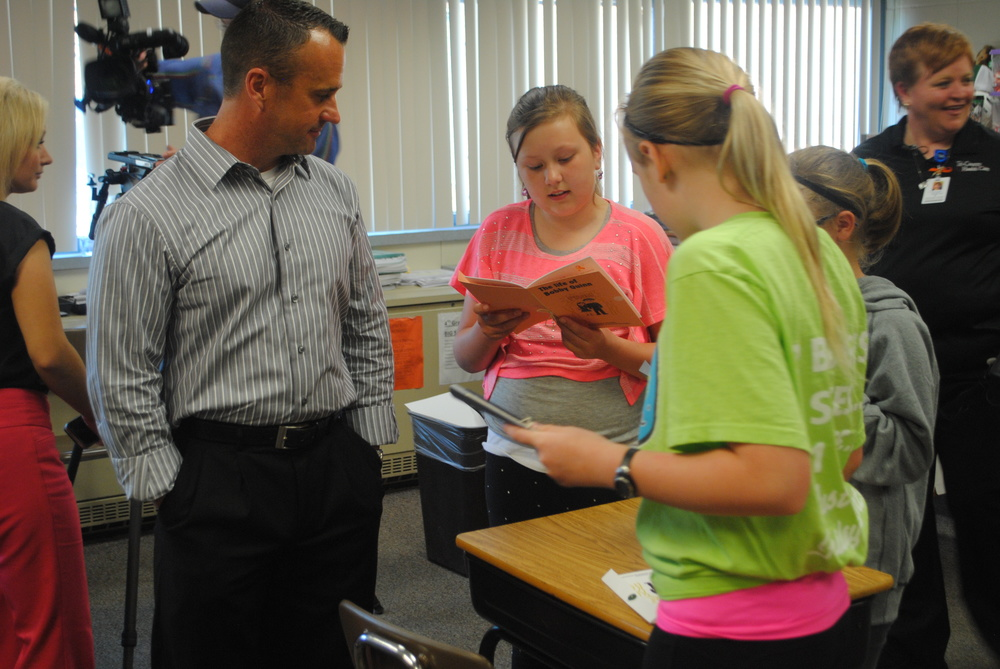 WDC Fourth-Grade Teacher Jeff Mehl, left, listens to Summer Pettit and her classmates as they anxiously page through the book. Mr. Mehl and Mr. Scott Woods helped the students finish their chapters for this unique and special book in memory of Jane Fiemeyer.