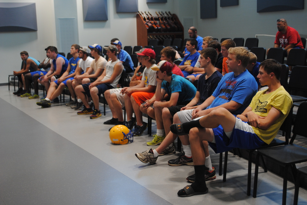 Players listen intently on the first evening of Wolverine Football Camp.