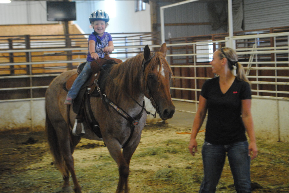 Leah Kircher is all smiles as she rides Ruby. Keeping a watchful eye is Sarah Madsen.
