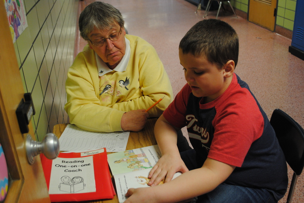 Reading one-on-one coach Carol Klindworth listens to a student read. The coaches help students improve their reading skills -- a valuable service to WDC students. (Photo by Dana Pavek, WDC Schools)