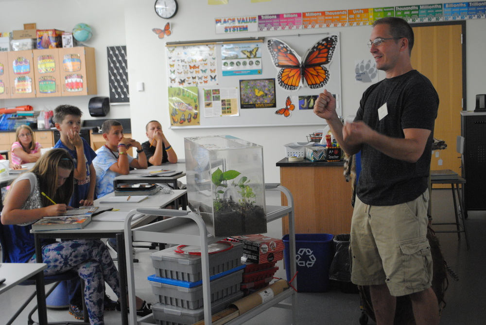 Steve Schmitz answers questions from WDC sixth-graders on Thursday about the five-lined skink he found on his Wadena farm (pictured in the large plexi-glass container on cart). (Photo by Dana Pavek, WDC Schools)