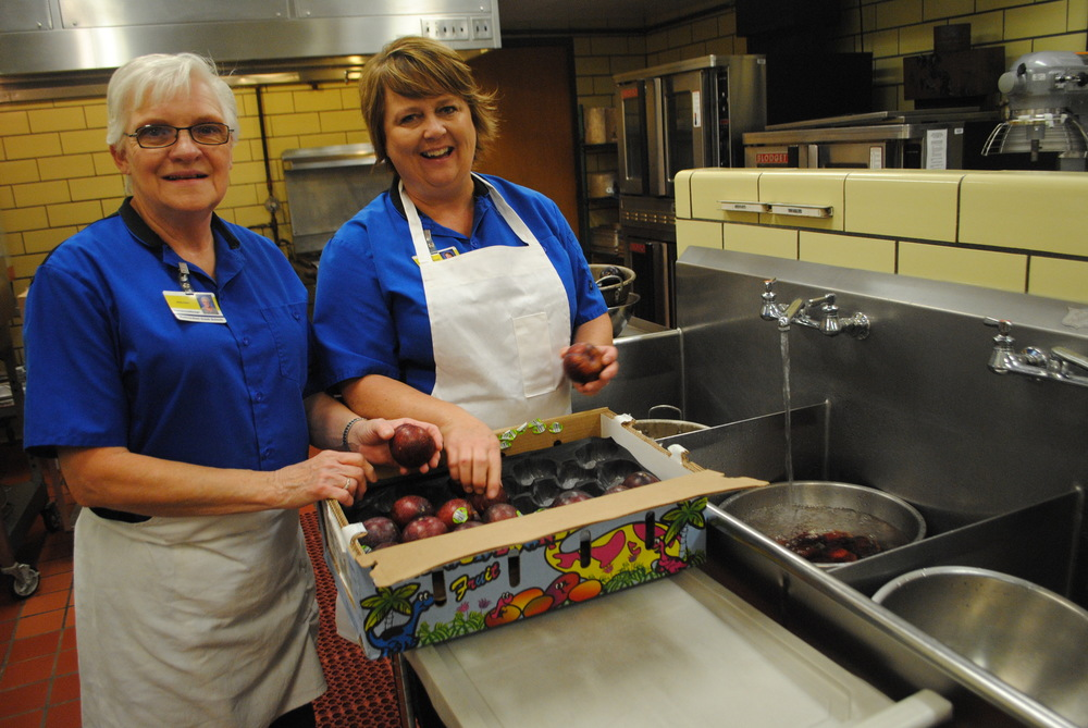 WDC Elementary cooks Arlis Kern and Nadine Wegscheid unpack and wash pluots for students' afternoon snack..