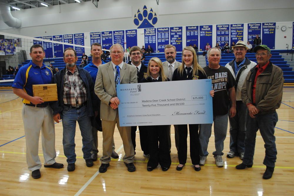 The $25,000 check from the Monsanto Fund was presented before the start of the WDC vs. Dilworth-Glyndon-Felton volleyball game on Oct. 13 at WDC Middle/High School. Pictured, from left:  Tyler Church, principal, Wadena-Deer Creek Middle/High School; Ed Lewis, greenhouse coordinator, Wadena-Deer Creek School District; Preston Dagen, district sales manager, REA Hybrids/Monsanto rep; Richard Muckala, agriculture instructor, Wadena-Deer Creek Middle/High School; Ethan Benson, FFA student; Madison Barthel, FFA student; Lee Westrum, superintendent, Wadena-Deer Creek School District; Olivia Schwartz, FFA student; Wayne Perkins, Deer Creek farmer/WDC School Board member; Dave Evert, Stimulating Economic Progress; and John David Bendix, Deer Creek farmer. (Photo by Dana Pavek, WDC Schools)