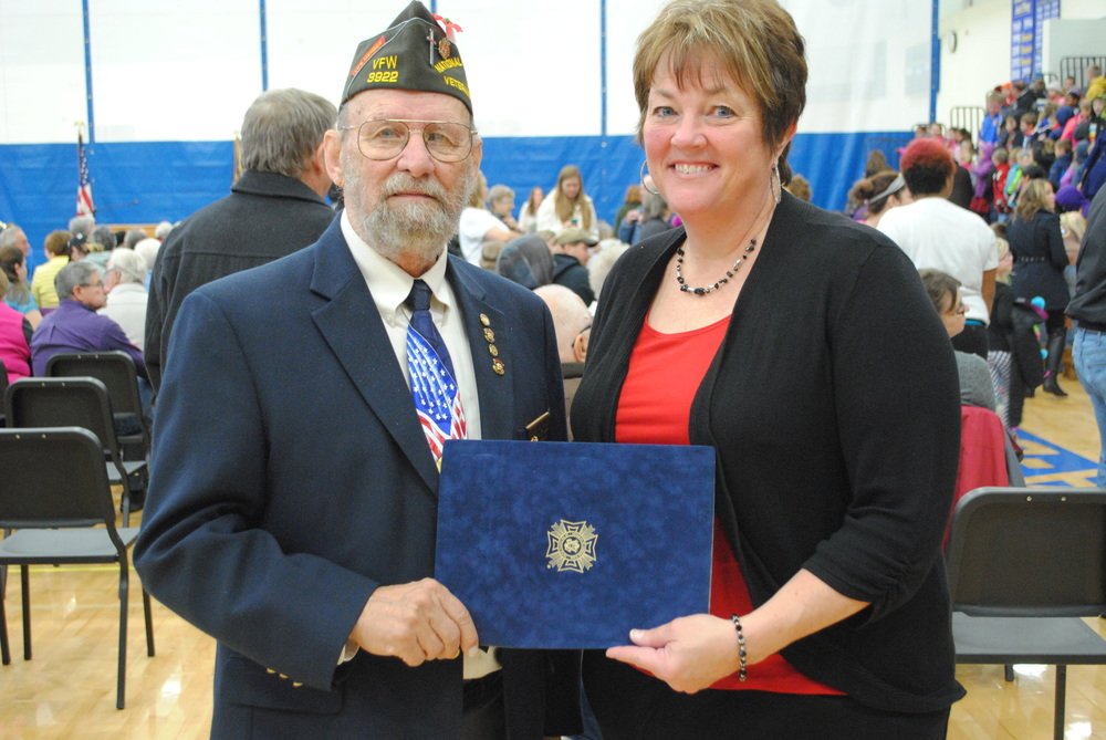 Wadena-Deer Creek Elementary teacher, Junelle Jackson, received her VFW Citizenship Education Teacher of the Year award from Jim White, Wadena VFW representative at the school's Veterans Day program. Jackson's award nomination was forwarded to the District level and she recently learned she'd won and will advance to the state competition. (Photo by Dana Pavek, WDC Schools)