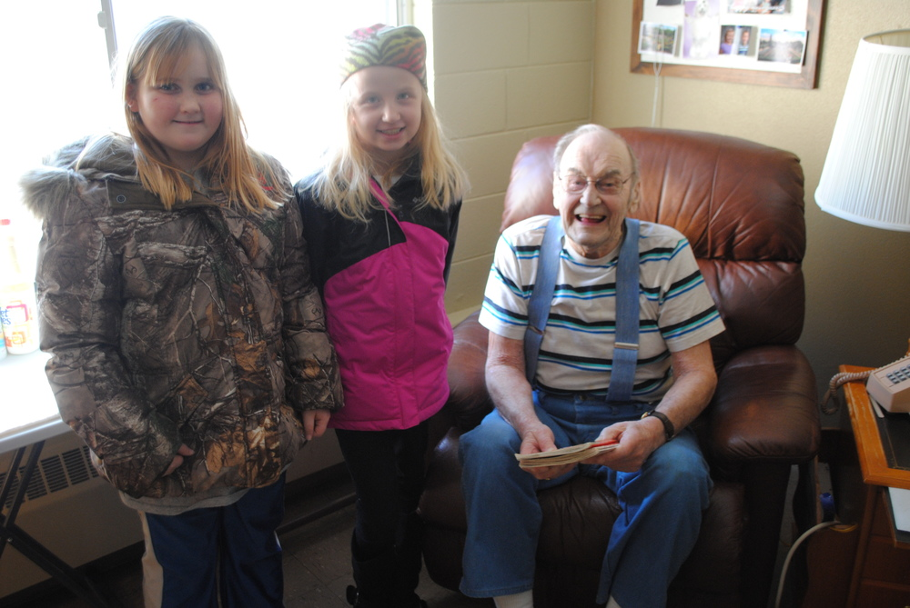 Third-graders Andrea Malone and Hannah Dosdall read Robert Swanson two books during their visit at Fair Oaks Lodge on Wednesday, Feb. 4. After the students finished reading, Swanson dug out a scrapbook and shared stories from his life as a policeman, a farmer and a commercial fisherman with the attentive students. (Photos by Dana Pavek, WDC Schools)