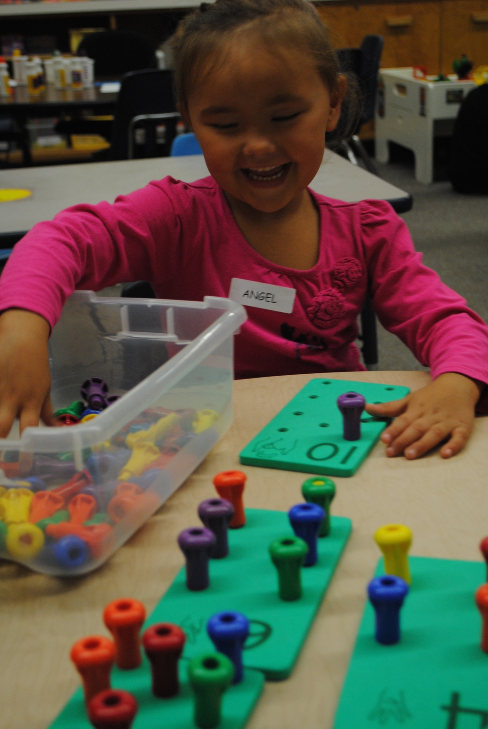 Angel Erickson, 4, has fun putting colorful pegs in number boards in Alicia Johnson's preschool class today. (Photos by Dana Pavek, WDC Schools)