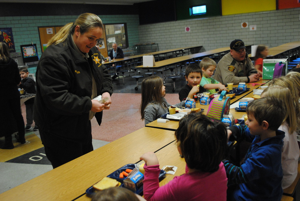 "Wadena County Sheriff's Department Dispatcher Erica Penner hands out ""junior badge"" stickers, while Conservation Officer Greg Oldakowski visits with students during the Law Enforcement Luncheon at Wadena-Deer Creek Elementary. (Photo by Dana Pavek, WDC Schools)"