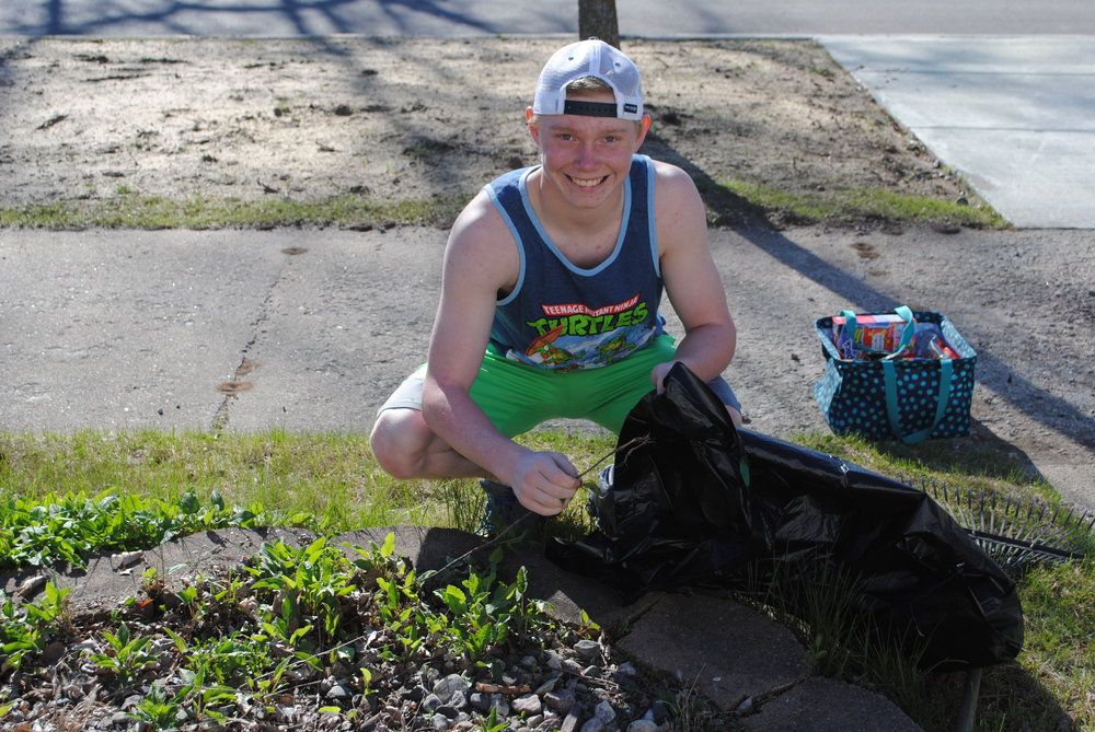 Preston Warren cleans a flower garden for an elderly resident last year.