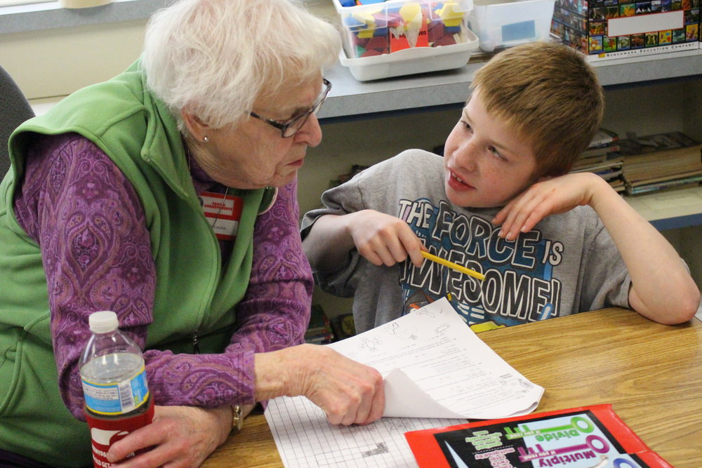 Foster Grandparent Leona Porter offers help to third-grader Ettore Pinnella with an Accelerated Math problem.