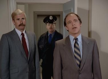Why does the officer on the left have different hair and mustache color