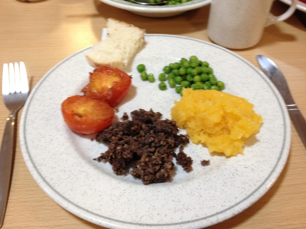 Haggis, mashed turnips, peas and grilled tomatoes