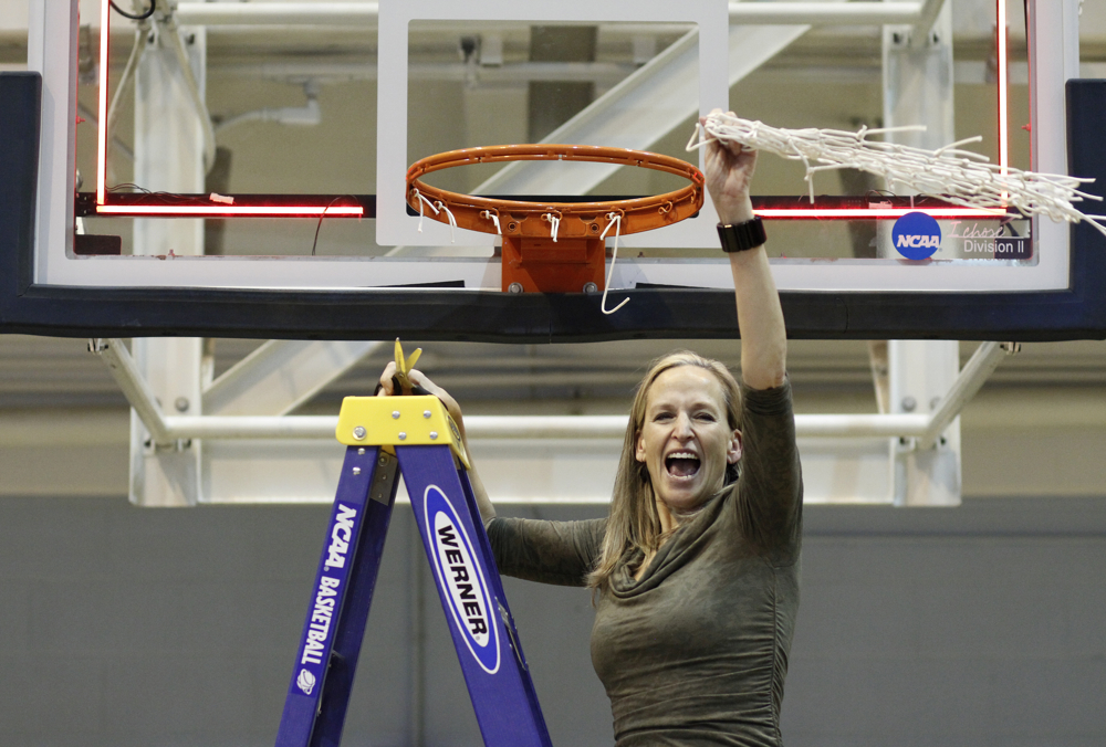 Western's head coach Carmen Dolfo waves the freshly cut net after the game. Each player cut a piece for themselves and Dolfo cut off the remaining. Western Washington University women's basketball team defeated Simon Fraser University 75-58, Tuesday, Feb. 19, 2013, during the final game of the NCAA II West Regional playoffs at WWU in Bellingham.
