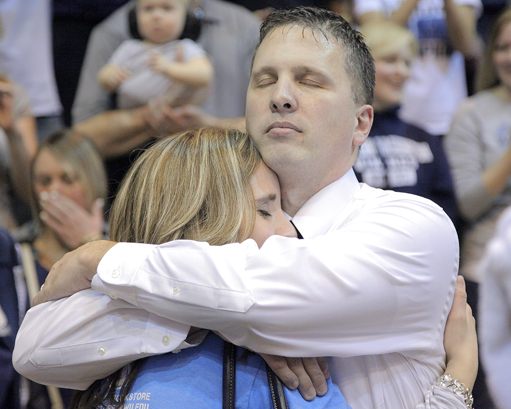 Amidst players and fans rushing the courts to celebrate Western Washington University men's basketball victory of Seattle Pacific University 62-58 in the NCAA II West Regional final, Western's head coach Tony Dominguez hugs his wife Kristi in a moment of bliss, Tuesday, Feb. 19, 2013, at WWU in Bellingham.