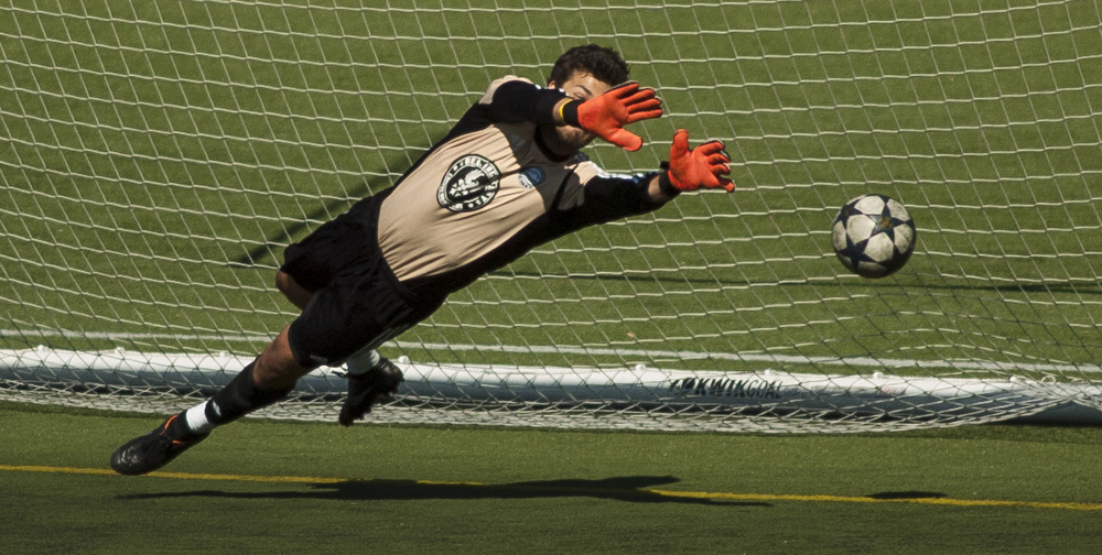 Bellingham United's Leo Cohen (1) dives to block a penalty kick that is just out of reach during the Hammers final regular season game. Bellingham United F.C. defeated Victoria Highlanders F.C. 2-1 in the Pacific Coast Soccer League, Sunday, July 21, 2013, at Civic Field in Bellingham. With the win against the Highlanders, the Hammers qualified to compete in the Challenge Cup, which will be played in July 27-28 in Coquitlam, British Columbia.