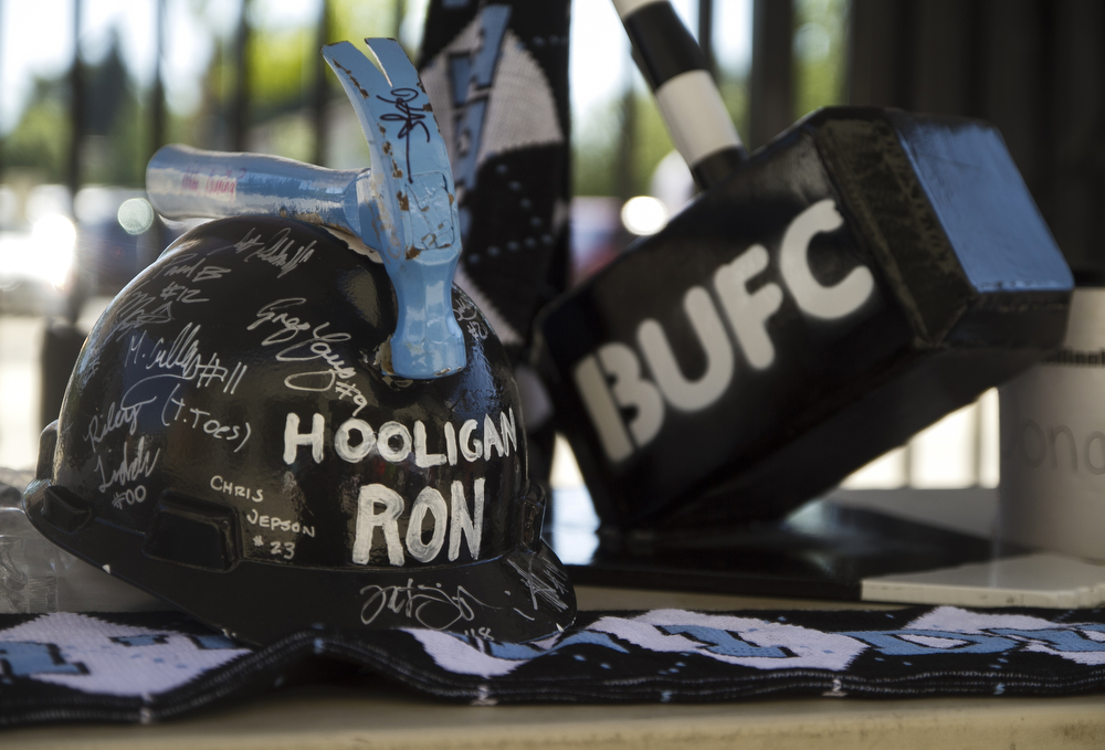 Hooligan Ron's supporter cap is displayed on the Bellingham United supporters table. Errien West, better known as Hooligan Ron, had last season's team sign his  iconic cap, made out of an old hard hat and hammer, during their first meet and greet.