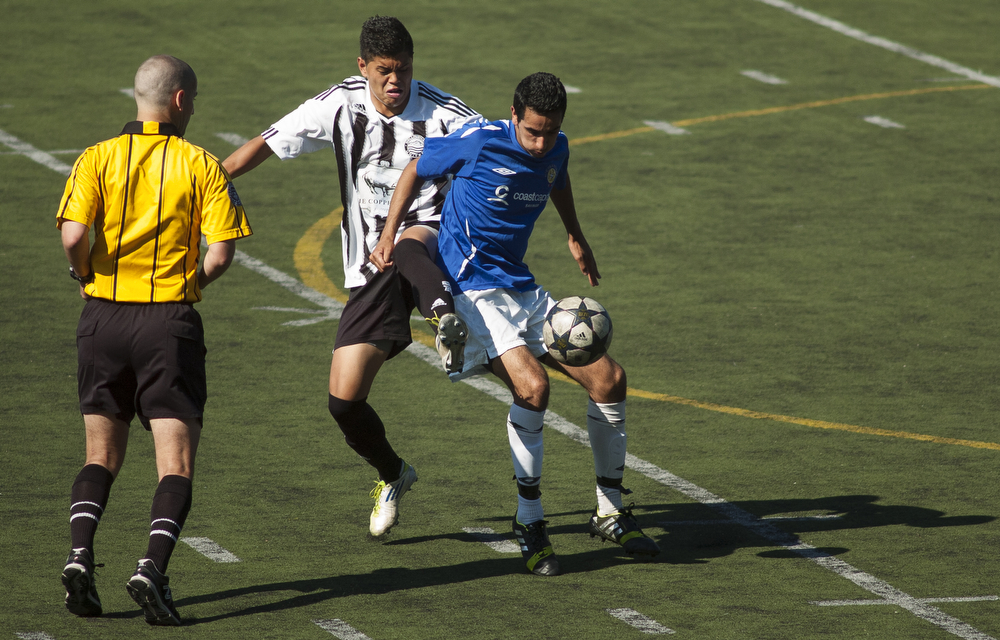 Bellingham United's Sunjinda Dangvan (10), center, and Victoria Highlanders' Tarnvir Bhandal (16) battle for the ball near midfield during the second half of the Hammers last regular season game. Bellingham United defeated Victoria Highlanders F.C. 2-1 in the Pacific Coast Soccer League, Sunday, July 21, 2013, at Civic Field in Bellingham. With the win against the Highlanders, the Hammers qualified to compete in the Challenge Cup, which will be played in July 27-28 in Coquitlam, British Columbia.