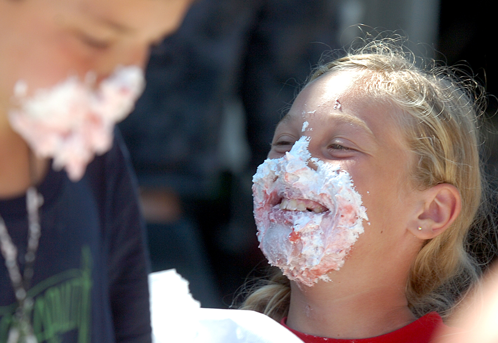 With a face full of strawberry whip cream pie, Gabriella MacKenzie, 11, of Bay View, right, smiles because she and Josiah Cantrell, 10, of Camano Island, left, tie for first place in a pie eating contest at the Skagit County Fair, Friday, in Mount Vernon. Nick Gonzales / Skagit Valley Herald