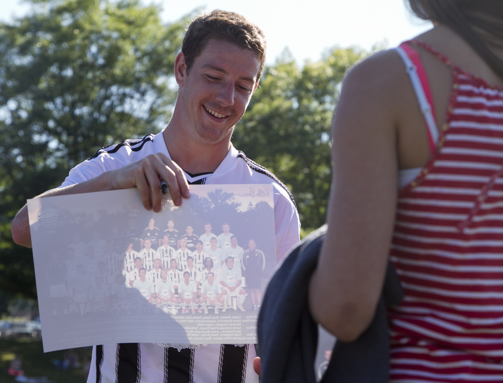 Kellan Brown signs a team poster for a young fan. Bellingham United F.C. defeated Victoria Highlanders F.C. 2-1 in the Pacific Coast Soccer League, Sunday, July 21, 2013, at Civic Field in Bellingham. With the win against the Highlanders, the Hammers qualified to compete in the Challenge Cup, which will be played in July 27-28 in Coquitlam, British Columbia.