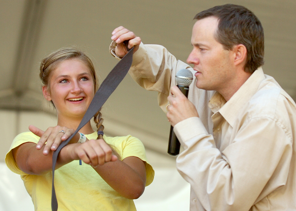 While hypnotized, Kendra Van Beek, 15, of Burlington, pets a belt which she believes to be a snake, during hypnotist Kerry Sharp's show on the main stage at the Skagit County Fair, Friday, in Mount Vernon. Nick Gonzales / Skagit Valley Herald
