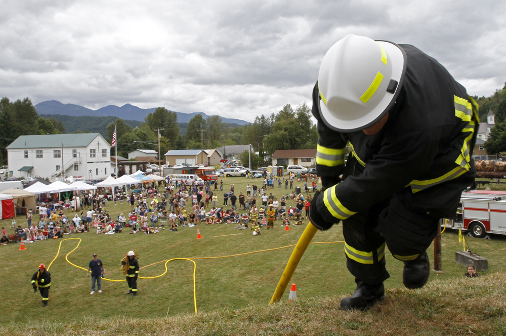 Mike Hockett, battalion chief for the Grassmere Fire Department, makes it to the finish line during the hill climb competition of the fireman's muster the Cascade Days on Saturday, Aug. 17, 2013, in Concrete, Wash. A parade, fireman's muster, Nick Gonzales / Skagit Valley Herald