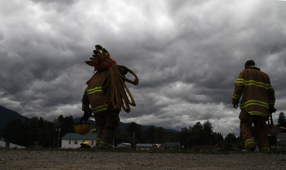 A firefighter carries a coiled up fire hose down a hill after completing a round of firemen's muster hill climb competition at Cascade Days, on Saturday, Aug. 17, 2013, in Concrete, Wash. Nick Gonzales / Skagit Valley Herald