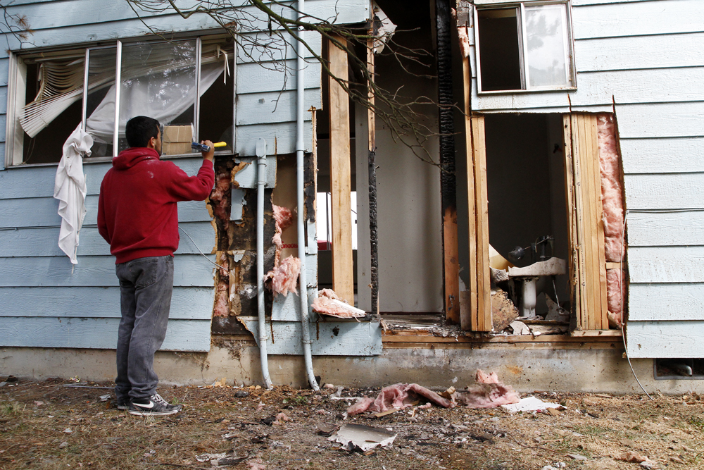 """Rodrigo Fernandez, neighbor in an adjacent apartment complex, helps clean up the the remains of an explosion on the 400 block of Stanford Drive, Friday, Aug. 16, 2013, in Mount Vernon, Wash. Police said an explosion happened shortly before midnight on Thursday, Aug. 15, when occupants were likely attempting to extract oil or """"hash"""" from a marijuana plant by mixing parts of it with butane in a two-liter pop bottle. Nick Gonzales / Skagit Valley Herald"""