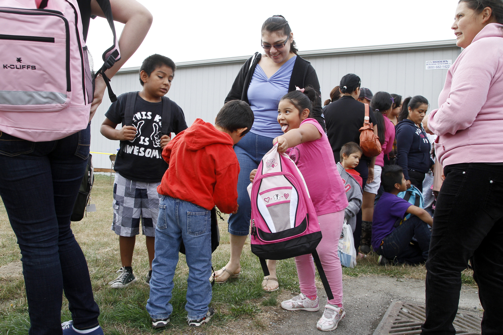 Daisy Maciel, 5, in pink, shows off her new backpack and school supplies to her brothers, Giovanni, 5, in red, and Mathew, 7, in black and mom, Leticia, at Back to School Blessing on Saturday, Aug. 17, 2013, at Mount Baker Middle School in Mount Vernon, Wash. Fred Meyer, Kwanis, Office Max, Advanced H20, Toys R Us, Bargains Galore and Neighbors in Need donated 1,000 free backpacks, school supplies, clothing, and 5,500 pounds of food to the cause put on by Mount Vernon area churches. A couple thousand people turned out for the event. Nick Gonzales / Skagit Valley Herald