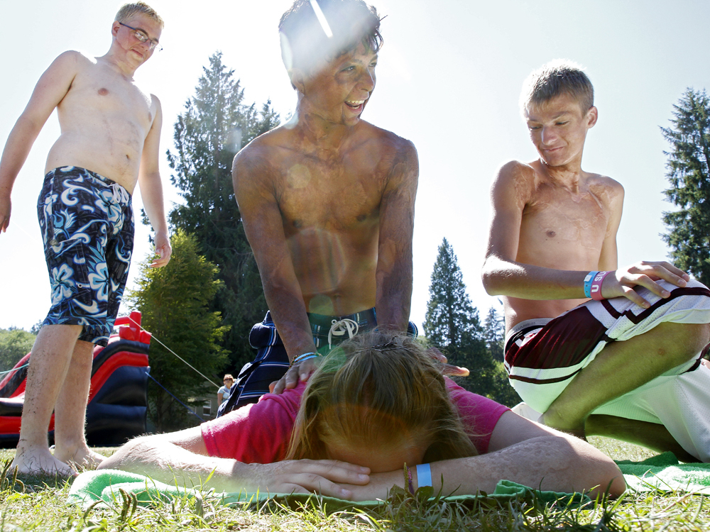 Justin Bigelow, 15, center gives Kayla Henson, 14, both of Texas, a massage as Jon Hibbs, 16, left, and Louie Heiges, 15, right, look on at Camp Phoenix, a summer camp for children with severe burns on Wednesday, Aug. 21, 2013, at Samish Lake in Bellingham, Wash. The week-long annual summer camp is aimed to help children emotionally recover from burn injuries. Justin sustained burns during a car fire a little more than a decade ago.