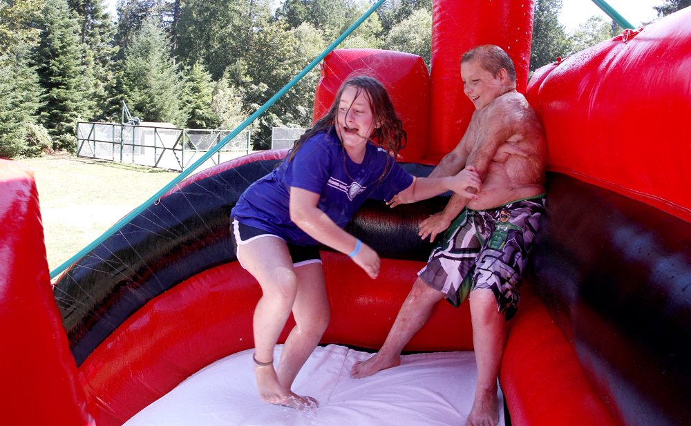 After trying to push each other down a giant inflatable water slide Wednesday, Austin Soder, 13, of Odessa, Texas, finds a safe spot in the corner as Jamie Bartok, 9, of Bellingham, turns to fall down the slide at Camp Phoenix at Lake Samish in Bellingham. The week-long annual summer camp helps children emotionally recover from their burn injuries. Nick Gonzales / Skagit Valley Herald