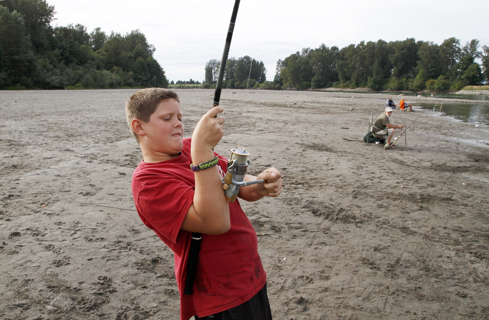 Dylan Yarnell, 12, reels in his first Pink salmon of the day on Wednesday, at Edgewater Park in Mount Vernon. The Yarnell family is vacationing in Deceptions Pass but visits Mount Vernon each summer to fish salmon in the Skagit River. The Skagit lower river opened Aug. 1 and the salmon season extends to December 31. Nick Gonzales / Skagit Valley Herald