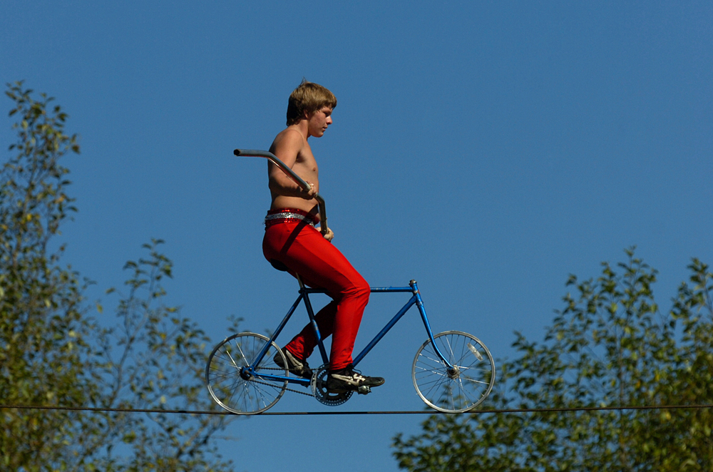 Mitchell Thacker, 15, rides a bicycle across the high wire during a Wenatchee Youth Circus performace at Thousand Trials on Saturday, Aug. 31, 2013, in Bow.