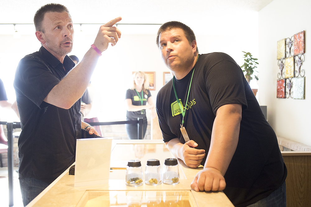 2020 Solution's first costumer Patrick Kalles, of Bellingham, points to the menu of cannabis strains and prices, on Thursday, July 10, 2014 in Bellingham. He settled on Blewetts, the least expensive option, which comes with three filtered pre-rolled cannabis for $42.