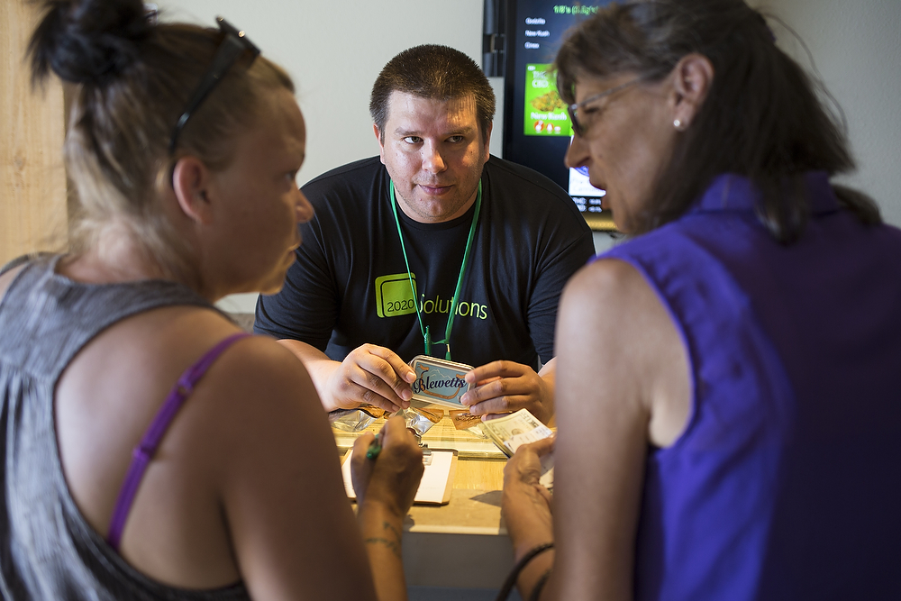 Employee Jorge Molina suggests Blewetts, to two costumers at 2020 Solutions on Thursday, July 10, 2014, in Bellingham.