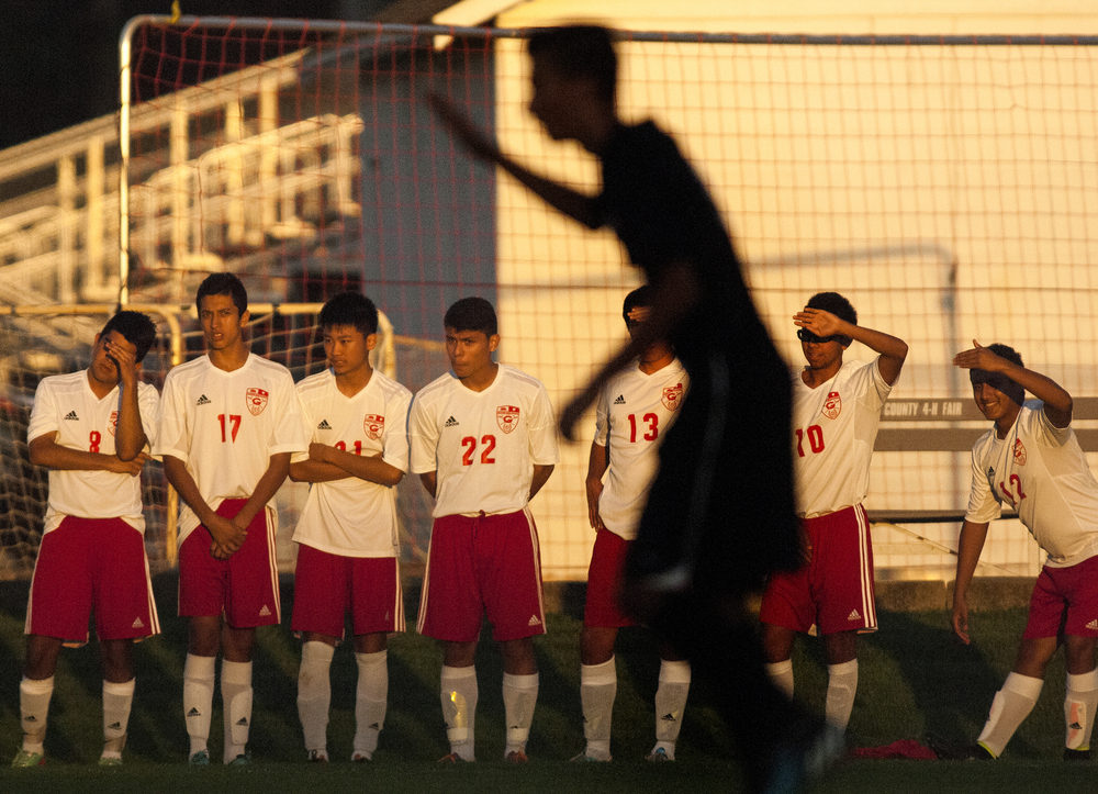 Seven Goshen players wait on the sideline waiting to be substituted in as a silhouetted NorthWood player raises his hand takes, signaling to his teammates that he's about to take a free kick on Thursday, Sept. 18, 2014, at Goshen. Goshen beat NorthWood 4-0.