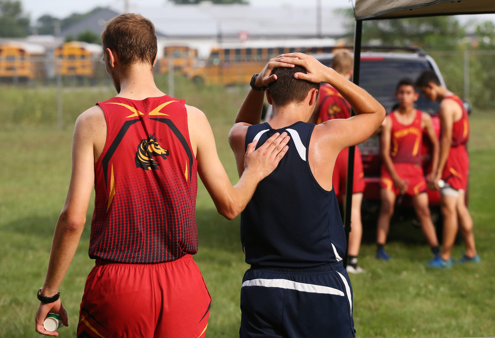A Memorial cross country runner, left, pats a Central runner on the back after he collapsed after a race on Sept. 4, 2014, at Memorial.