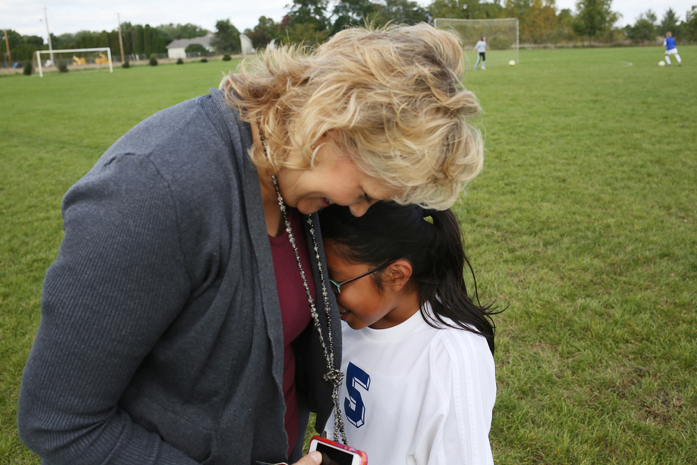 Marsha King nuzzles with her daughter Reyna King, 10, before a middle school soccer game on Tuesday, Sept. 16, 2014, at Bethany Christian School in Goshen. The Kings decided to send their children to private school because the class sizes are smaller, more individual attention, and it re-enforces their Christian values, Said Tony King, Marsha husband.